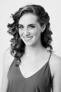 Black and white picture of a woman with curly hair smiling at the camera