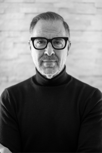 Black and white photo of man in dark frame glasses looks at the camera