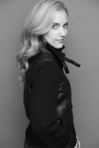 Black and white photo of a woman with blonde wavy hair looking at the camera over her shoulder