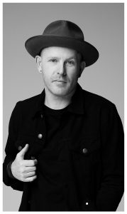 Black and white photo of a man in a hat looking at the camera