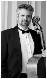 Black and white photo of a man in a suit with a cello