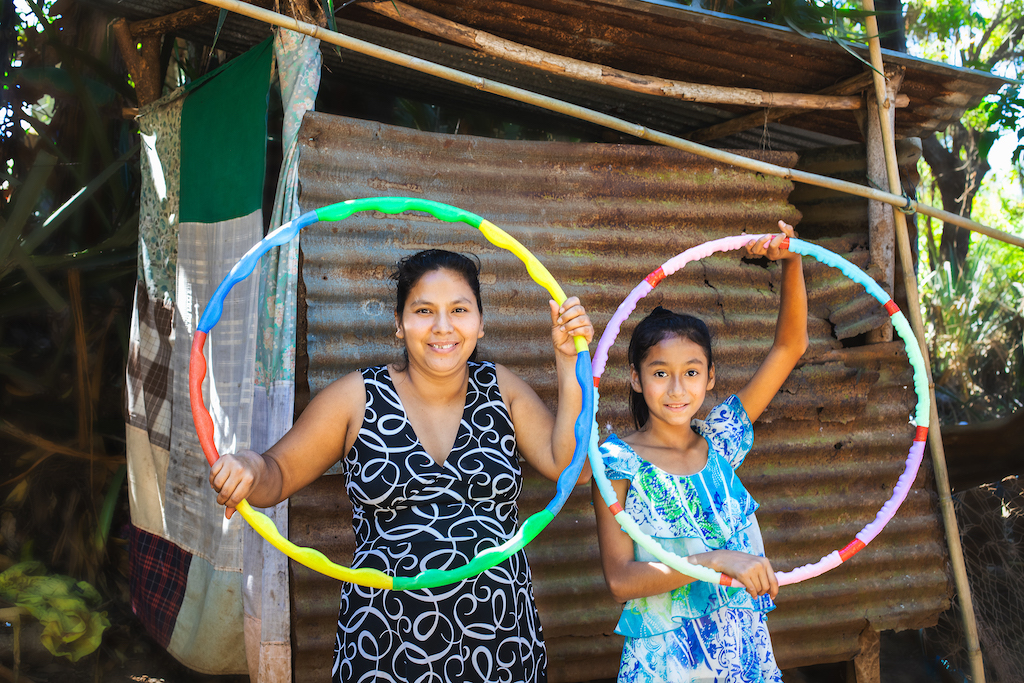 Suleyma is wearing jeans with a colorfully patterned shirt. She is standing outside her home with her mother, wearing a navy and white shirt. They are both holding up hula hoops.