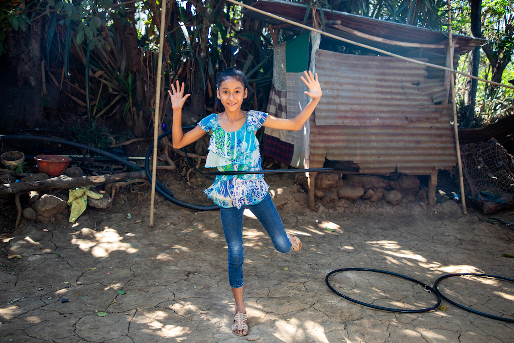 Suleyma is wearing jeans with a colorfully patterned shirt. She is standing outside her home and is playing with her hula hoops.