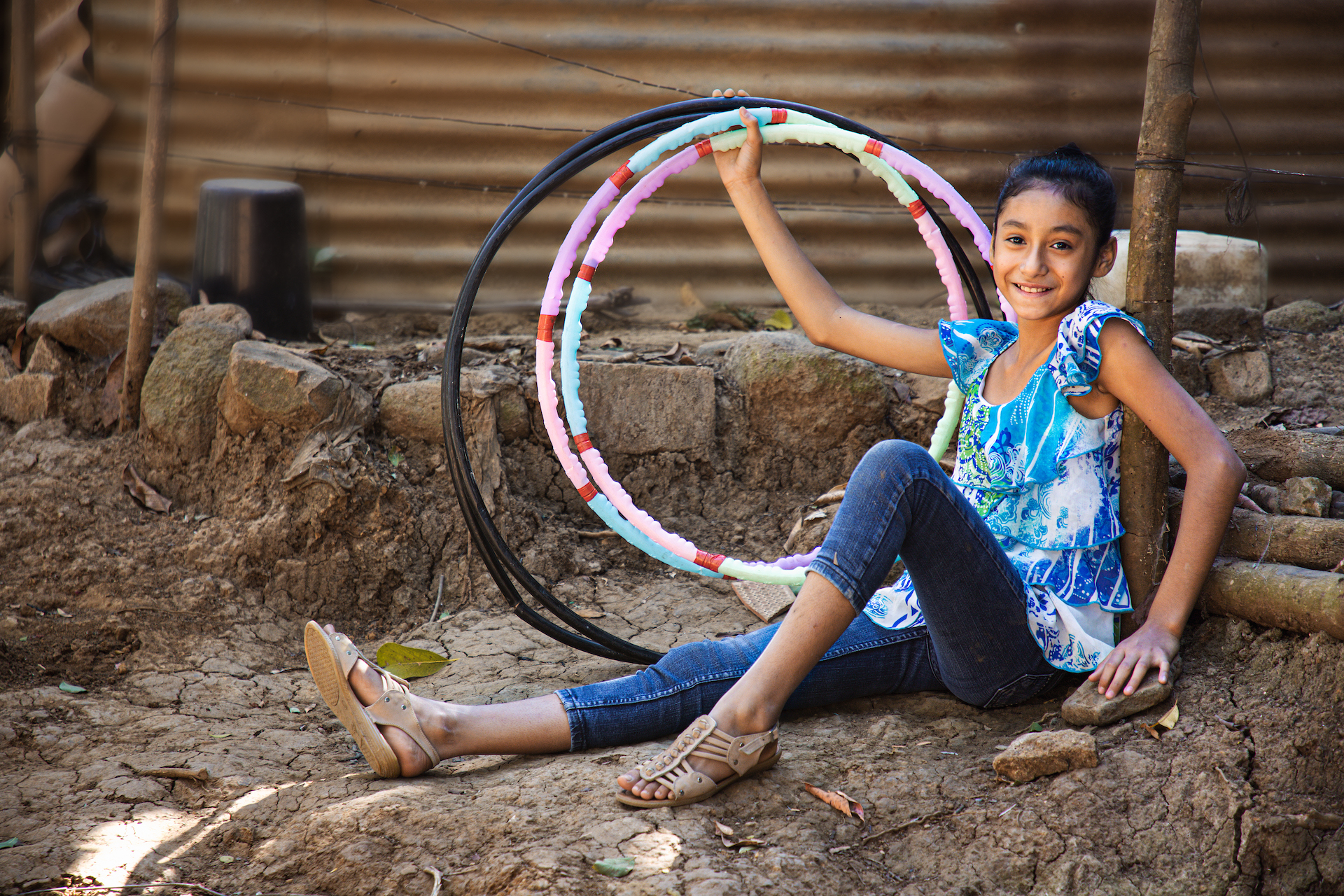 Suleyma is wearing jeans with a colorfully patterned shirt. She is sitting in front of her home and is holding several hula hoops.