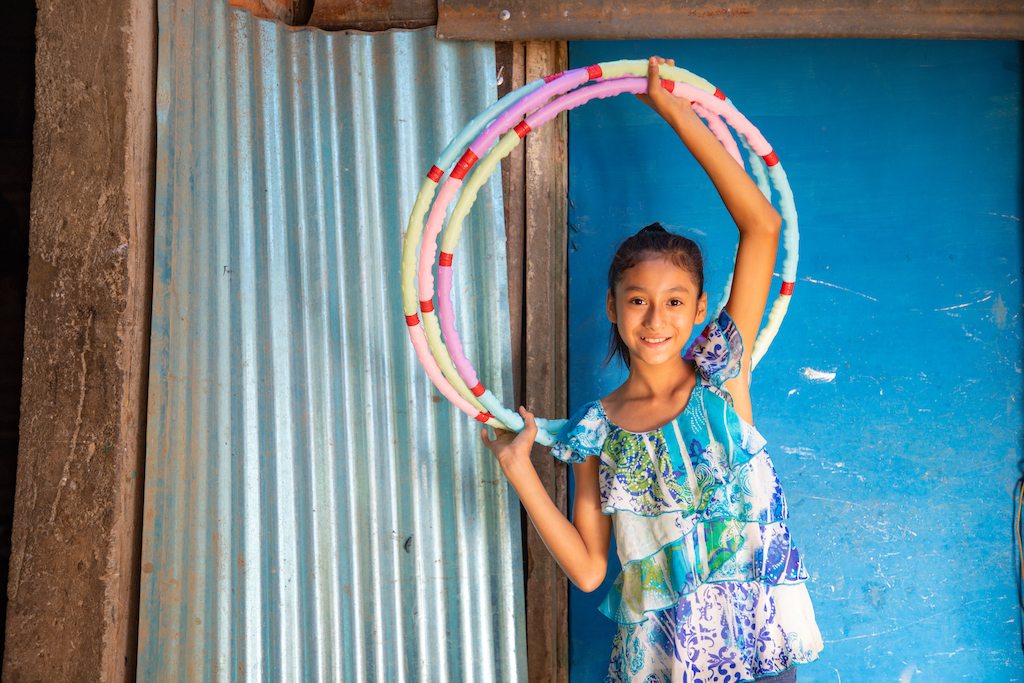 Suleyma is wearing jeans with a colorfully patterned shirt. She is standing in front of her home and is holding three hula hoops above her head. Her home is blue and the door is made of corrugated metal.