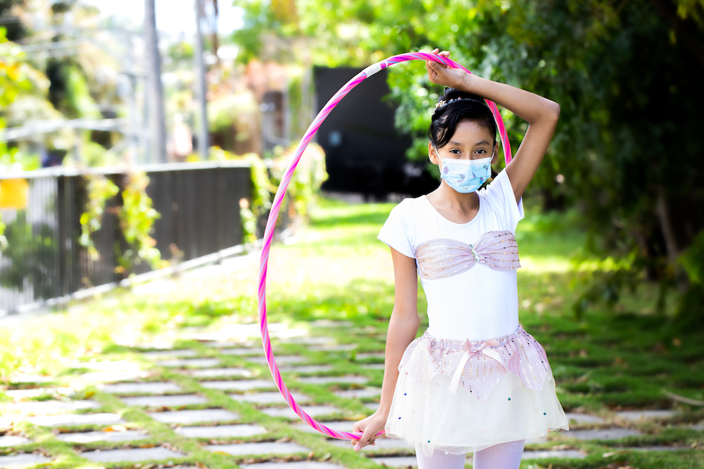 Suleyma is wearing her spinning uniform, a pink and white outfit, and a face mask. She is standing in front of a Compassion office where she is gettign ready to perform. She is holidng a hulu hoop over her head.
