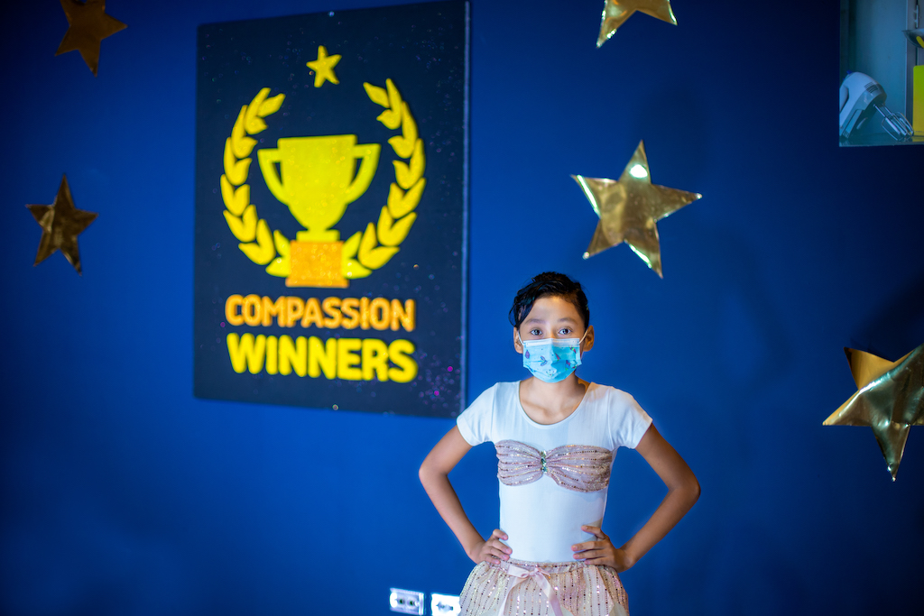 Suleyma is wearing her spinning uniform, a pink and white outfit, and a face mask. She is standing in a Compassion office preparing to give a performance. She has her hands on her hips and behind her there are stars on the wall and a sign that says Compassion Winners.
