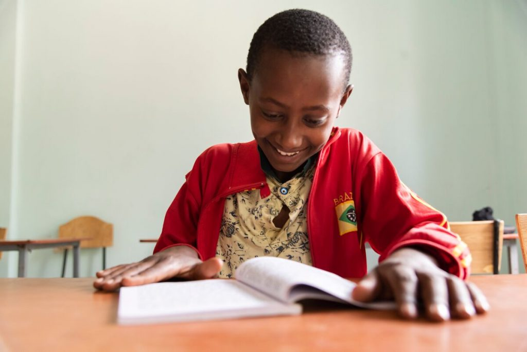 Abel, in a red jacket, is sitting at a table smiling and reading a book.