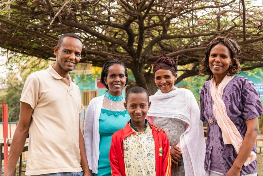 From left to right: Abaya (Project Director), Shahitu (health worker, in a blue dress), Astede (Abel's mom, in white), Meseret (social worker, in purple) and Abel (in red) are standing outside posing for a picture in front of a tree.