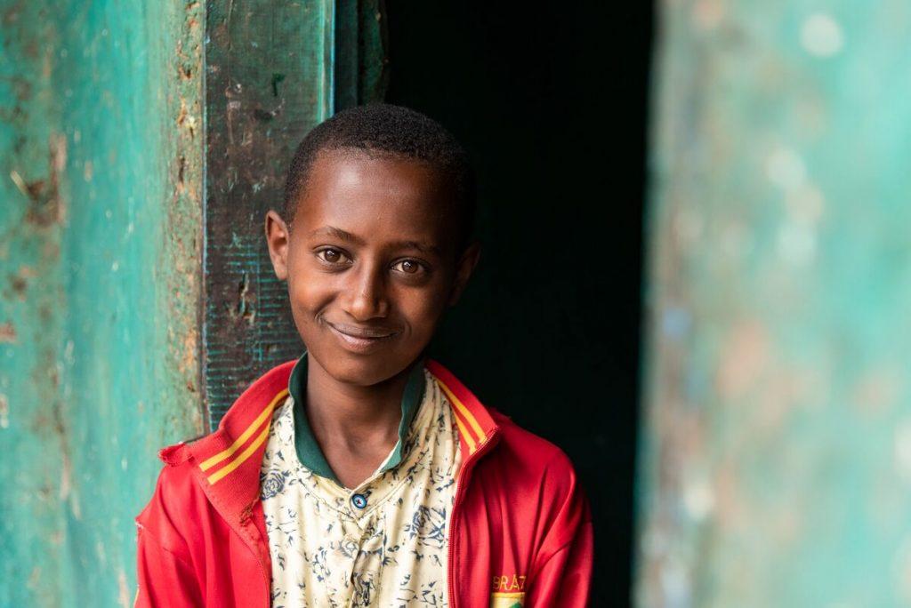 Abel, in a red jacket, is standing in blue-green, teal doorway, smiling.
