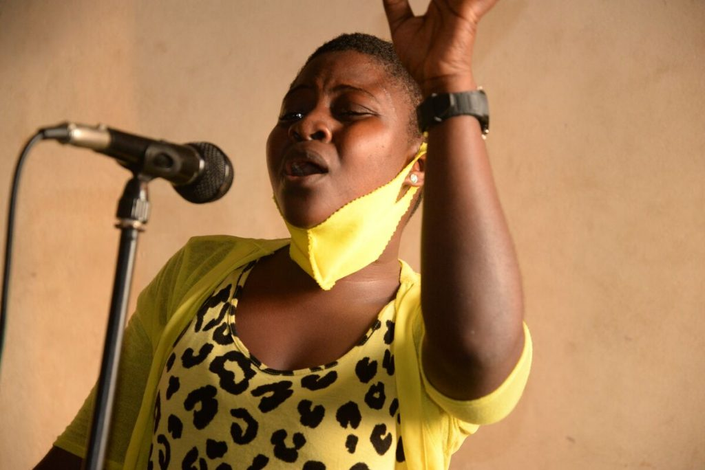Rosaline is wearing a yellow and black print dress and a yellow face mask. She is singing with a microphone and has one hand in the air.