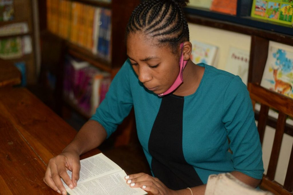 Abigael is wearing a black dress with a green jacket, as well as a pink face mask that is down around her chin. She is sitting at a table and is reading a book in the Compassion center's library. Behind her are book shelves.