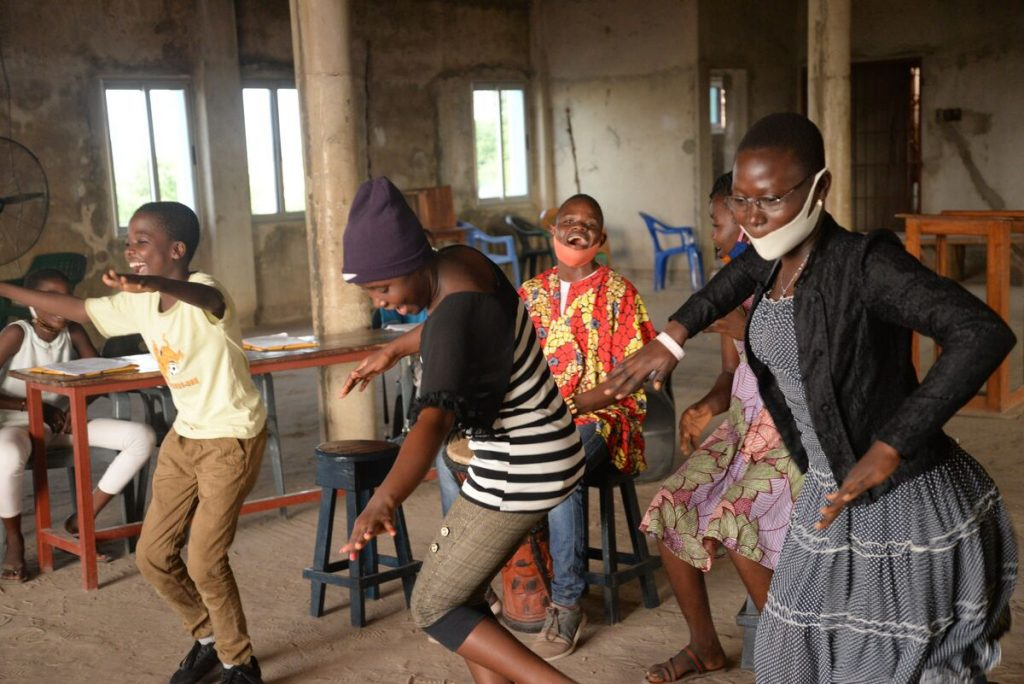 A group of youth are dancing inside the Compassion centre.