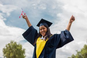 Maribel is wearing her graduation uniform, a black cap and gown, and a yellow collar. She is standing outside with her arms up in the air. In one hand is her diploma.