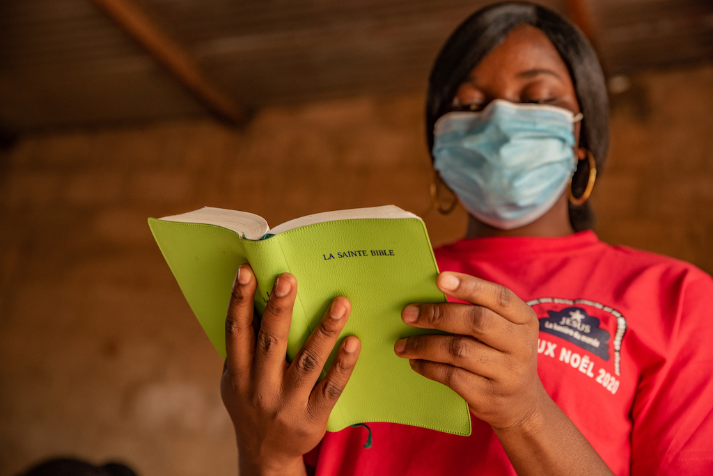 Rainatou is wearing a red shirt and a face mask. She is inside the center and is reading her green Bible.
