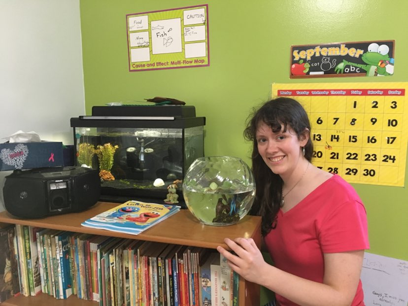 A woman in a red tshirt stands in a green classroom beside a fishbowl