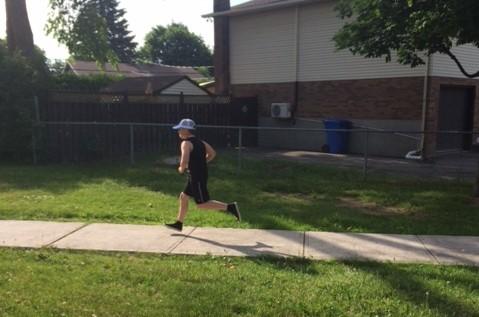 Boy in a white cap is running on a sidewalk