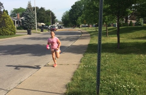 Girl in a pink shirt is running on a sidewalk