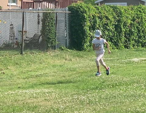 Girl in a white cap is running on the grass