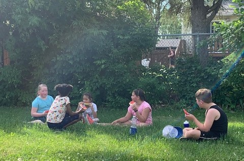 Kids sit on the grass eating watermelon