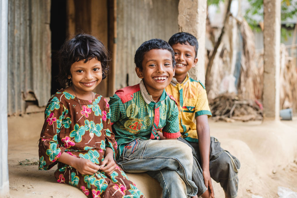 Three young siblings sit on a step in front of their home.