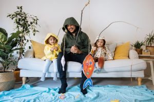 Two young kids are sitting on a couch with their father, all dressed in raincoats and pretending to fish.