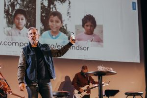 Pastor Brad stands on stage during a church service holding up a smart phone and inviting church members to sponsor a child with Compassion.
