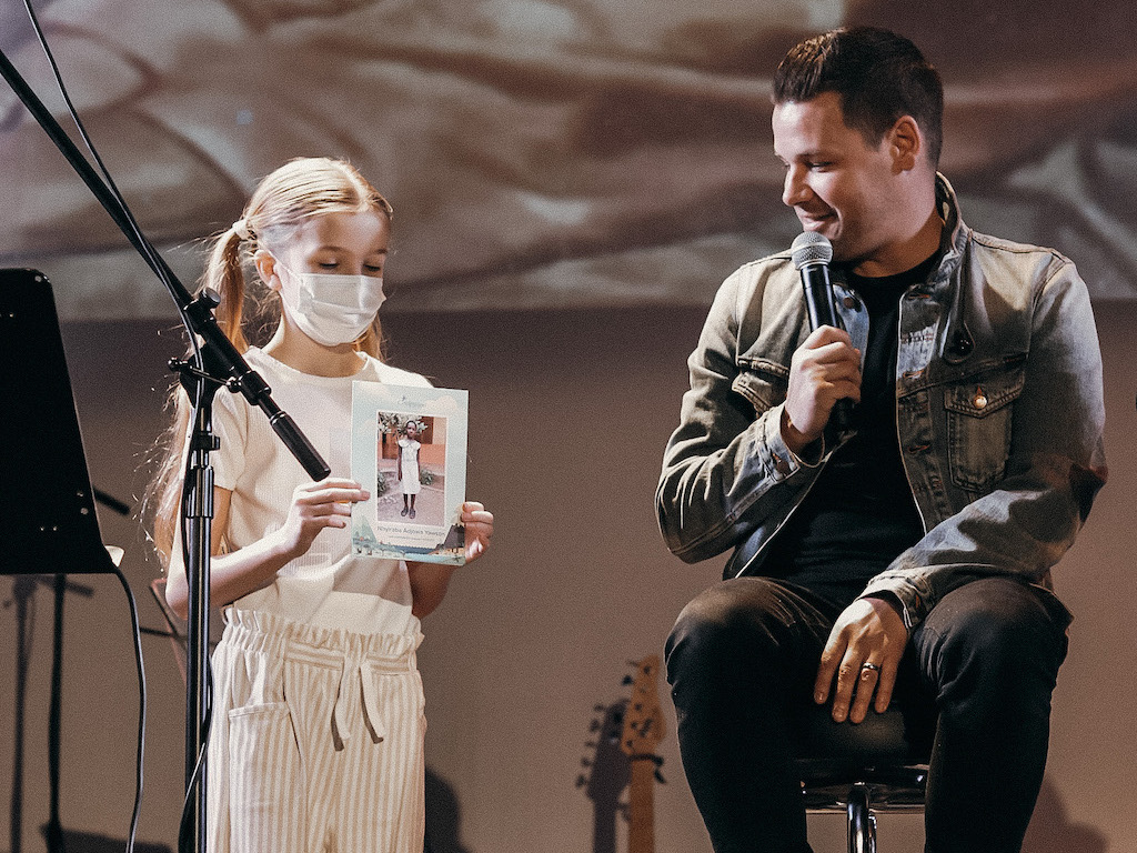 Pastor Drew sits on a stool on stage next to his daughter who is standing and holding up a photo of their family's Compassion sponsored child.