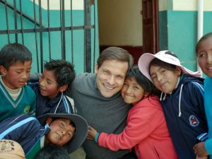 A man smiles at the camera with a group of children all smiling