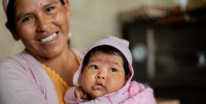 A Bolvian mother holds her healthy baby, who has beautiful, chubby cheeks and smiles.