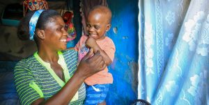 A Haitian mother carries her son on her hip and laughs.