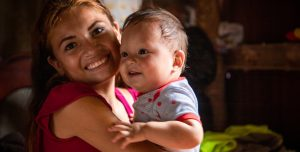 An Ecuadorian mother holds her smiling baby boy and smiles too.