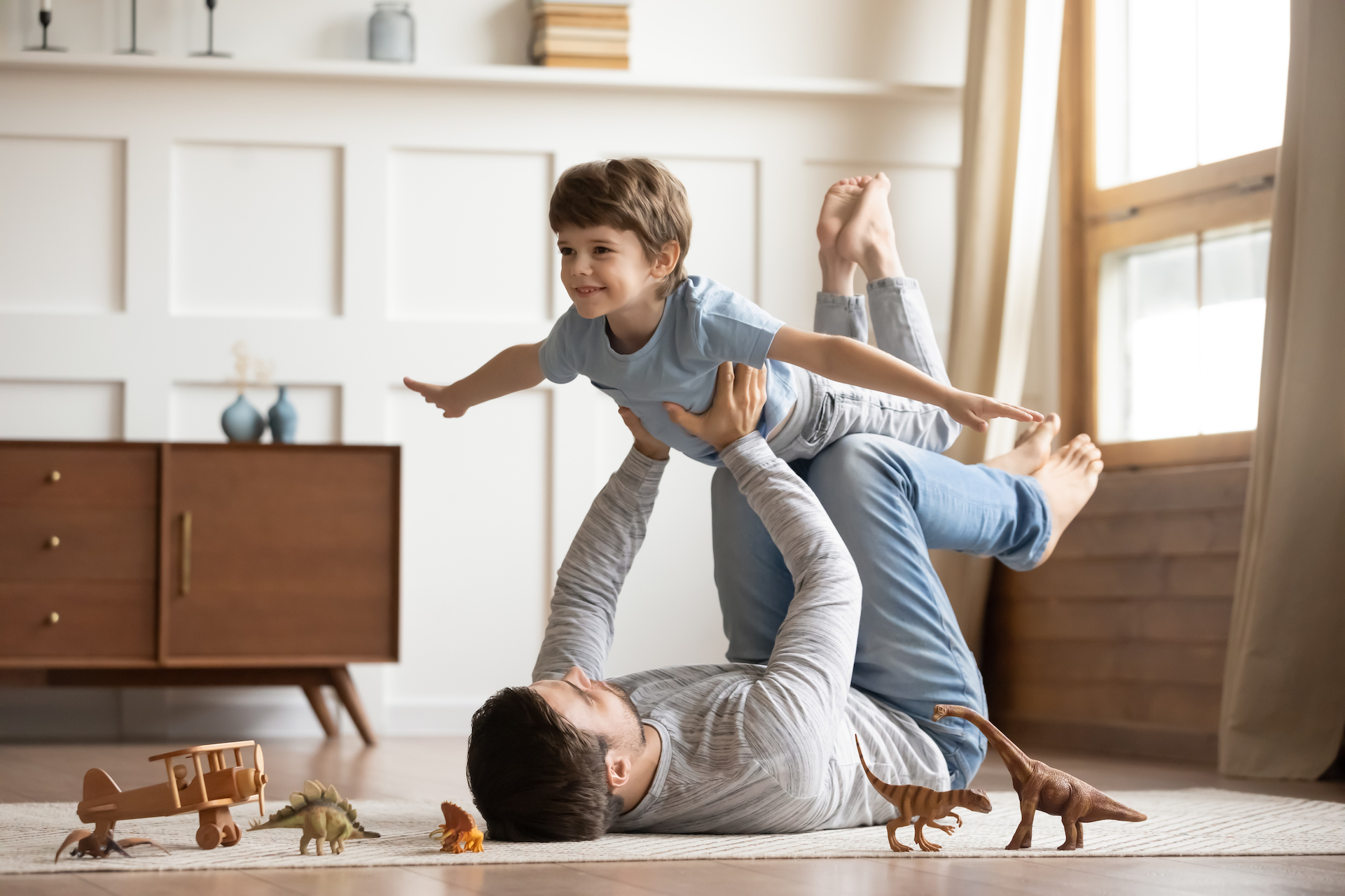 A father lying on the floor of a living room lifting up his young son as they play together.