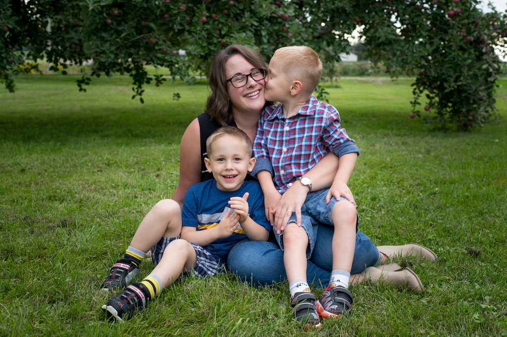Christine and her twin boys sitting on the grass.