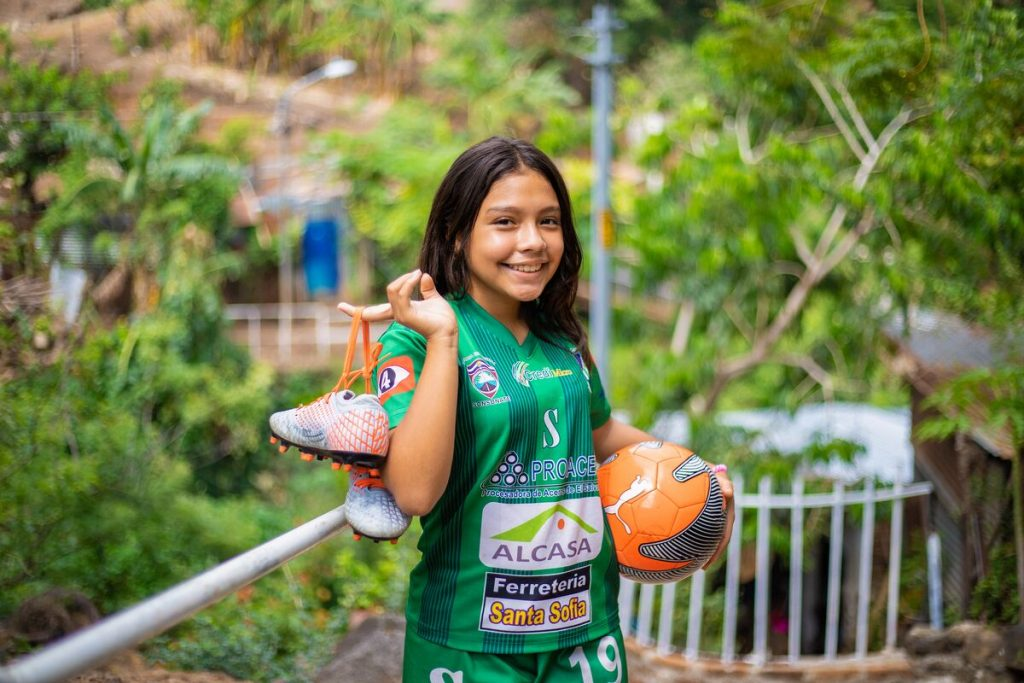 A young girl smiling while holding her soccer equipment.
