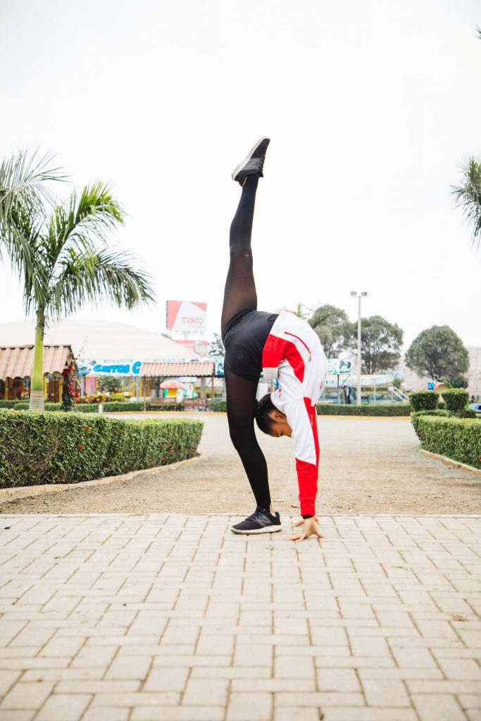 A young girl striking a gymnastic pose.