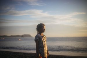An Indonesian girl stands on a beach at sunset.