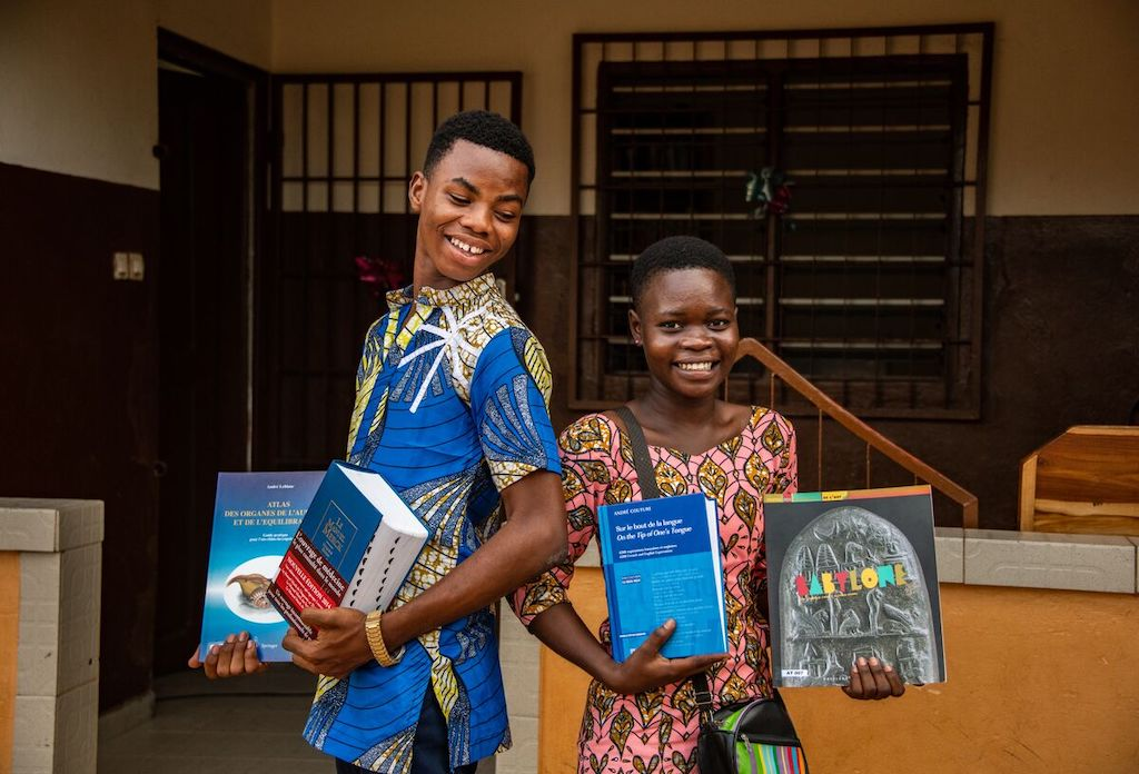 Two teens in Togo stand holding up their textbooks.