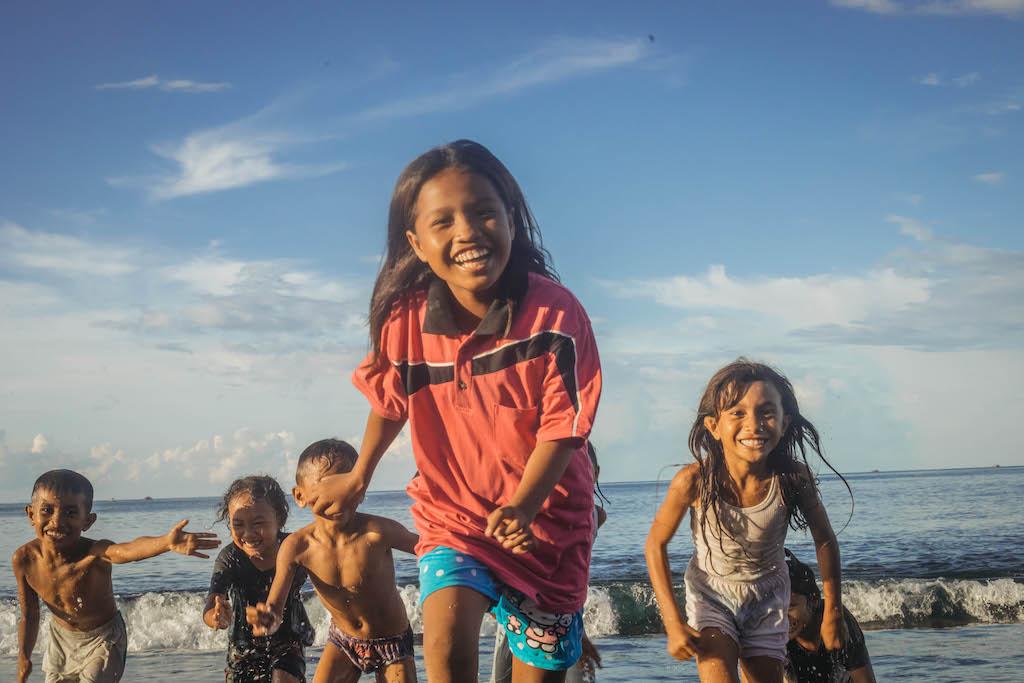 Children run on a beach in Indonesia.