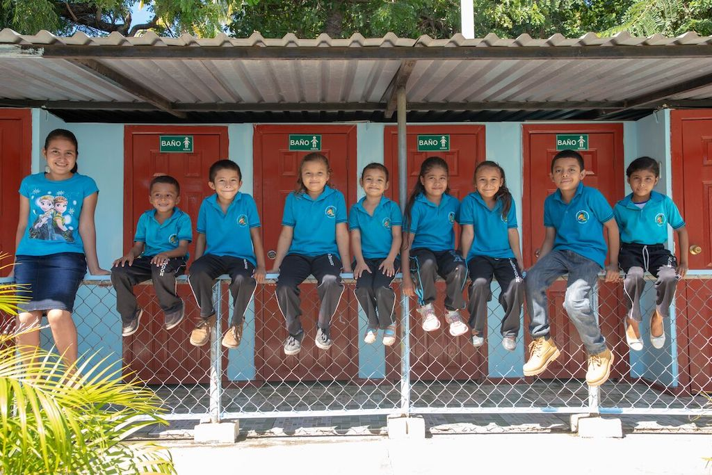 Kids in El Salvador sit on a bench in front of a newly-constructed washroom block in their community.