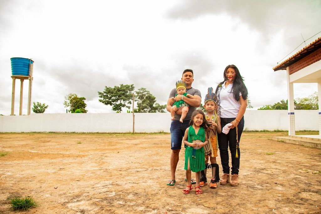 Cacique Magno is standing outside with his wife Michelly, and his children Kaio, Kaila, and Mayara during an indigenous festival.