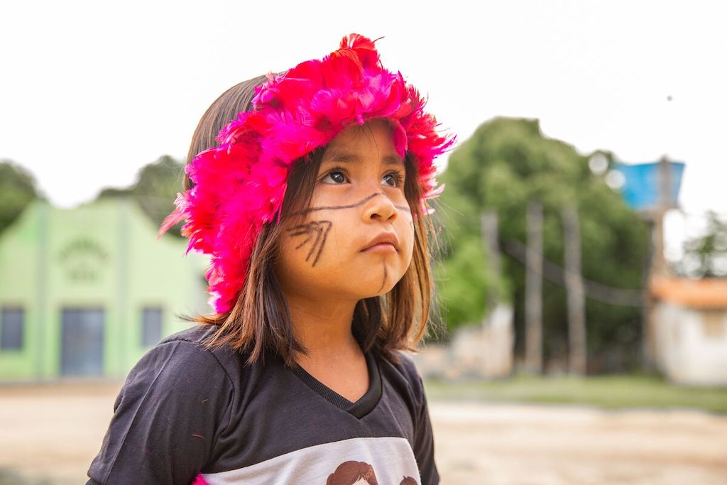 Suleany is standing in her neighborhood wearing a traditional head covering. She has her face painted.