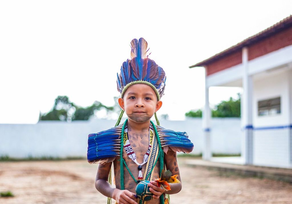 Kaio is standing outside the Compassion centre and is wearing a traditional Guajajara outfit. He is also holding a rattle. His face and body are painted with traditional designs.