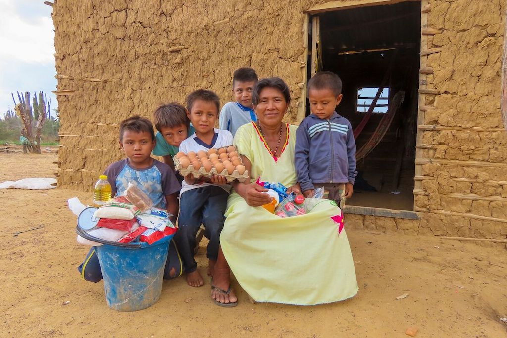 Alirio is wearing a white shirt and holding a tray of eggs. He is sitting outside with his mother and his siblings. There is a bucket of food in front of them which was provided by Compassion.