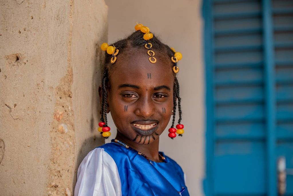 Oureira is wearing a blue and white traditional dress with red and yellow beads in her hair. She is also wearing black makeup on her face.