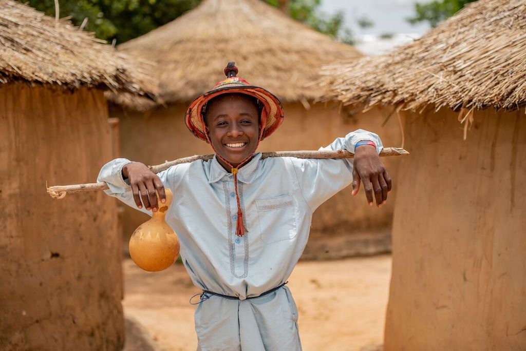 Abdoul is wearing yellow pants and a long light blue shirt with a hat. He is carrying a stick and a calabash cup. He is standing in front of three huts in his community.
