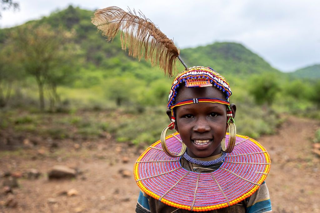 Salina is wearing a dress made with goatskin and a beaded head piece. She is standing outside her home. There are green hills and trees behind her.