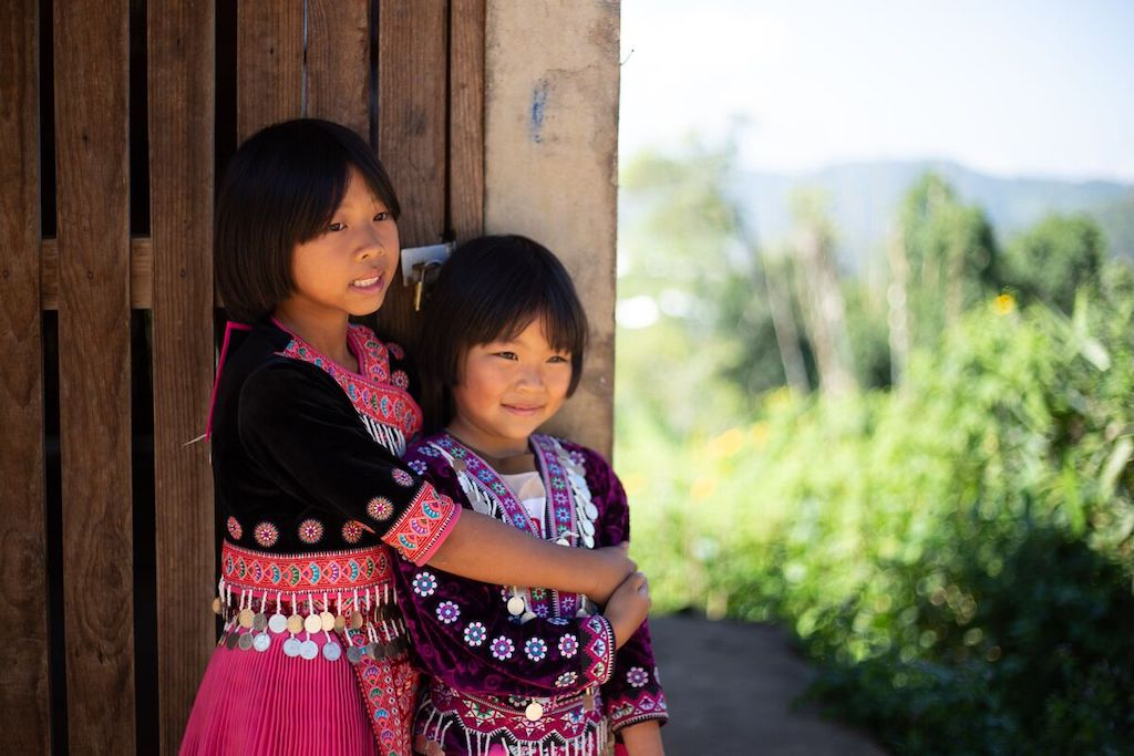 A close up of Nareerart, wearing a maroon traditional Hmong dress. She has her arms around Torfan who's wearing a purple traditional Hmong dress. They are both standing at the Compassion centre, looking off into the distance and smiling.