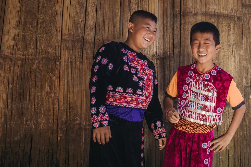 Two boys standing at the Compassion centre wearing their Hmong traditional dress, laughing with each other.