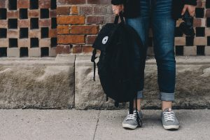 A teenager wearing jeans and sneakers and holding a backpack.
